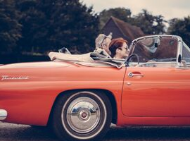 man and woman riding in a red classic convertible