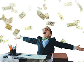 Excited young boy in a suit with out stretched arms surrounded by money.