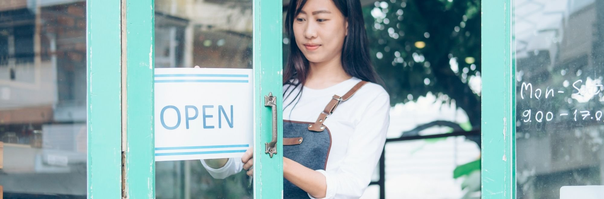 Woman hanging up Open sign in front door.